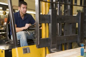 Warehouse worker in forklift